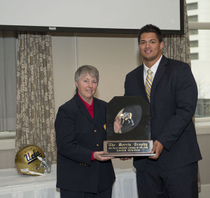 Traci Morris presents the 2013 Morris Trophy to UCLA tackle Xavier Su'a Filo